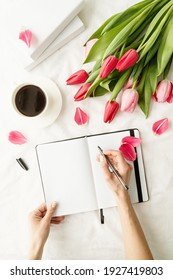 Holiday and celebration. Spring holidays. Woman hand making notes in opened notebook, decorated with tulips, coffee cup and books, top view flat lay