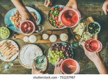 Holiday celebration table setting with wine snacks. Flat-lay of friends hands eating and drinking together. Top view of people having party, gathering, celebrating with rose champaign