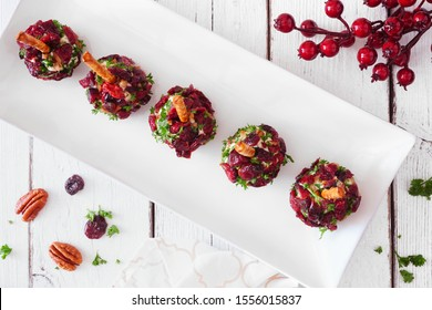 Holiday cheese ball appetizers with cranberries, pecans and herbs. Top view on a serving plate with a white wood background.