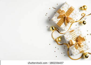 Holiday Christmas banner. Xmas background with luxury gift boxes, bright gold ribbon, glitter confetti stars, golden balls on white table. Flat lay, top view.