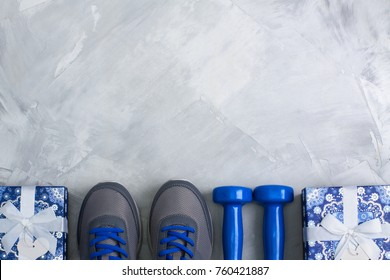 Holiday christmas birthday party sport flat lay composition with gray shoes, blue dumbbells and blue gifts on gray concrete background. Top view, horizontal orientation