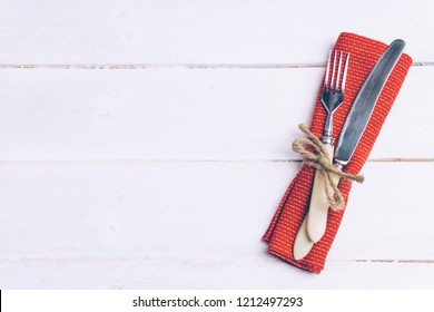 Holiday Christmas food background concept. Christmas table setting with a set of cutlery knife and fork on a red napkin with xmas decorations. White wood background. Christmas menu concept