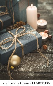 Holiday Christmas Gifts with Boxes, Candle, Snow, Coniferous, Basket, Cinnamon, Pine Cones, Nuts on Wooden Background.