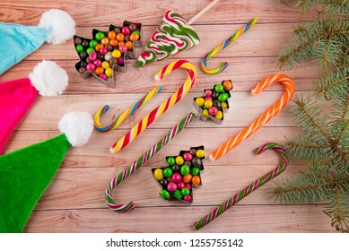 Holiday Christmas, New year sweets and cande canes laying on wooden table near colorful Santa, elf hats and fir tree branch