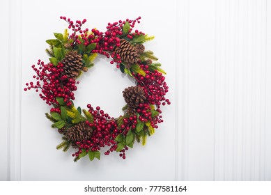 holiday christmas wreath with pine cones and red berry on a wall
