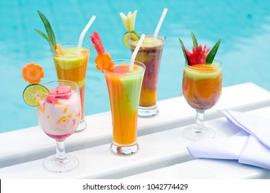 holiday coktails in the pool side with blue background water