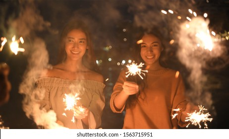 Holiday concept. Asian girls playing fun fireworks on the beach. 4k Resolution.