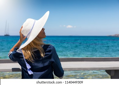 Holiday concept: attractive, blonde woman with white hat enjoys her summer holiday at the blue sea