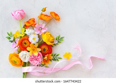 Holiday concept with bouquet of spring flowers on pastel vintage background. Easter composition, flat lay.