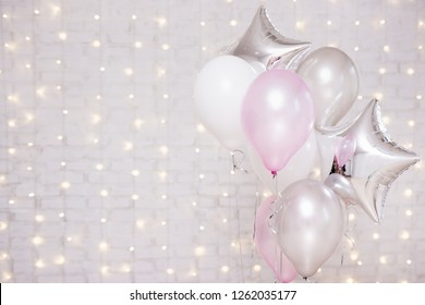 holiday concept - close up of colorful air balloons over brick wall background with lights