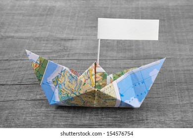 Holiday concept for cruising, traveling, sailing - blue paper boat of a map for a greeting card or a voucher, coupon