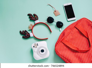 Holiday concept : Flat lay of Christmas ornaments and red woman bag open out with accessories and smartphone on green background with copy space