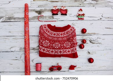 Holiday concept : Flat lay of Christmas ornaments and red woman jumper with accessories on white rustic wooden  background with copy space