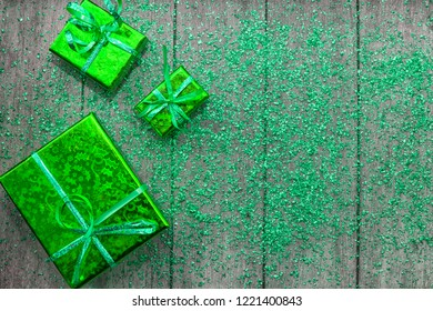 Holiday concept with green gift boxes and green sparkles on wooden background