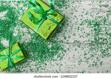 Holiday concept with green gift boxes and sparkles on a white wooden background