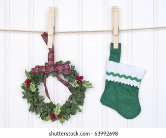 Holiday Concept with Holly Berry Wreath and Stocking Hanging on a Clothesline.
