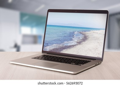 Holiday concept lenely laptop in the office showing beautiful resort pictures