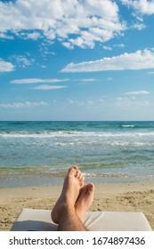 Holiday concept. Man feet close-up relaxing on beach, enjoying the sun.  Enjoying sun lounger on sunny summer day.