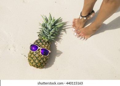 Holiday concept. Pineapple with sunglasses in a  Caribbean beach
