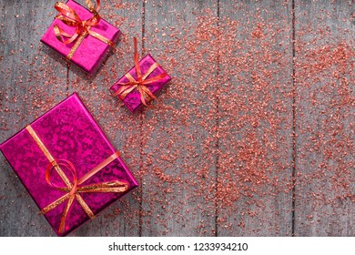 Holiday concept with pink gift boxes and pink sparkles on wooden background