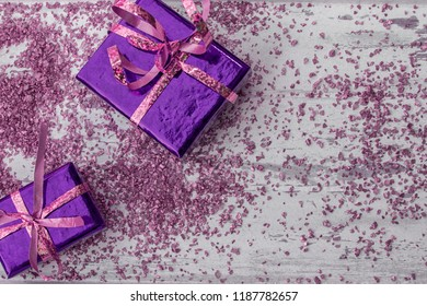 Holiday concept with pink and purple gift boxes and purple sparkles on a  wooden background