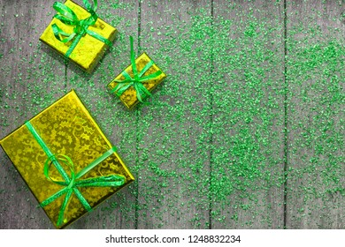 Holiday concept with yellow boxes and green sparkles on wooden background