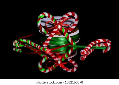 Holiday crafts, Pipe Cleaner candy canes with spools of red and green ribbon against a black background on a reflective black surface. with room for copy at top left and top right.