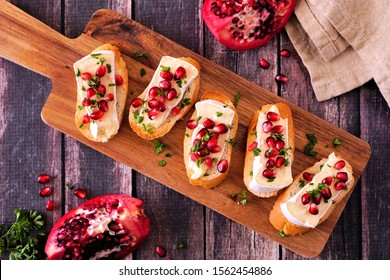 Holiday crostini appetizers with brie cheese, pomegranates and parsley. Above view on a serving board against a rustic wood background. Party food concept.