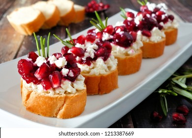 Holiday crostini appetizers with cranberries, pomegranates and feta cheese. Close up on a serving plate against a wood background.