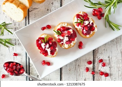 Holiday crostini appetizers with cranberries, pomegranates and feta cheese. Above view on a serving plate over a white wood background.