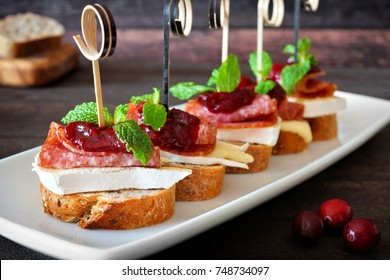 Holiday crostini appetizers with cranberry sauce, brie, salami, and mint on white serving plate against rustic wood