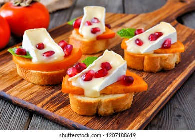 Holiday crostini appetizers with persimmons, pomegranates and brie cheese. Close up, side view scene on a wood background.