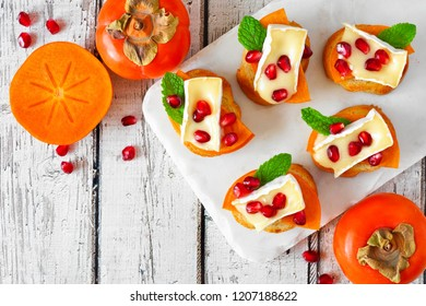 Holiday crostini appetizers with persimmons, pomegranates and brie cheese. Top view scene on a white wood background.