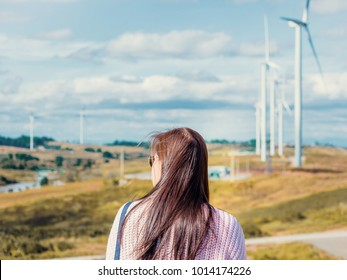 holiday dating and couple activity with backside of asian woman with sunglasses travel stand pose and see to sky for her boyfriend take photo with wind turbine background
