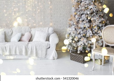 Holiday decorated room with Christmas tree and armchair with blanket. White interior with lights.