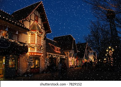 Holiday decorated shopping district in a German village with huge snowflakes falling from a deep blue sky.  Lighted wreaths and strings of christmas lights surround the doorways and windows.