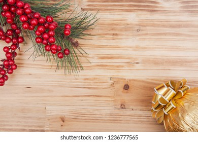 Holiday decoration - pine and berry bush with Italian chocolate ball wrapped in metallic gold foil and topped with golden ribbons and bows on wooden background