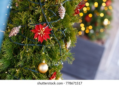 Holiday decorations and decor on fir tree branches with blurred light bulbs in the background