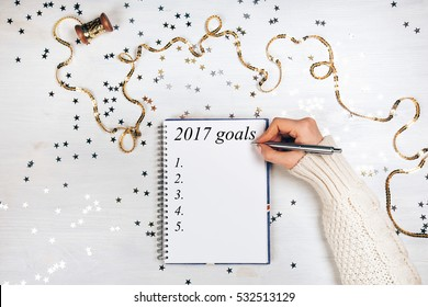 Holiday decorations and notebook with 2017 goals on white rustic table, flat lay style. Christmas planning concept.
