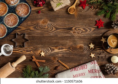 Holiday decorations on wooden table. Cupakes, cup of coffee, red christmas tree toys, cookies in shape of star, cinnamon, berries, branches of furry spruce. Image for greeting card. Copy space.