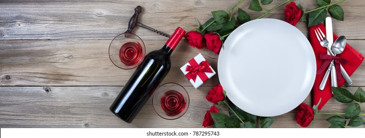 Holiday Dinner setting with red wine and roses on rustic wood in flat lay view