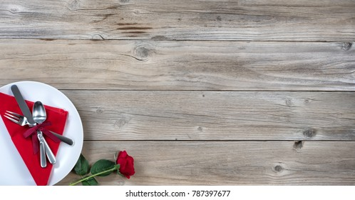 Holiday Dinner setting with single red rose and silverware in lower left corner on rustic wood in flat lay view