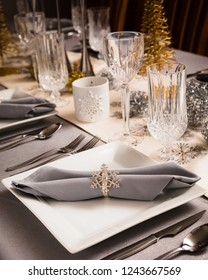 Holiday Dinner Table set with gold and silver decorations.  Grey cloth napkins with silver snow flake rings.