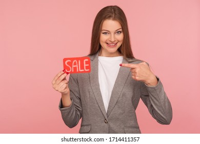 Holiday discounts for business client! Portrait of elegant lady boss in suit jacket pointing at Sale word, promoting low cost, best price products, Black Friday shopping. indoor studio shot isolated