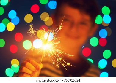 Holiday dynamic postcard. A happy boy holds a lighted fireworks on a blurred background of a bright Christmas garland. Meeting the new year. Christmas evening