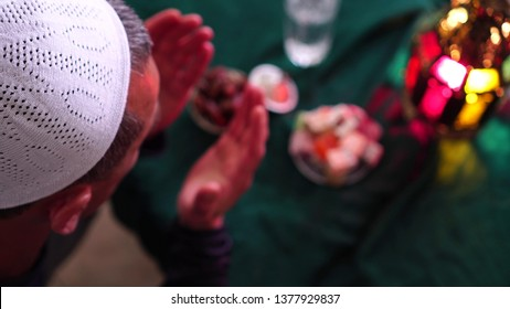 The holiday of Eid al-Fitr. Muslim man prays and breaks the fast. Islamic Dua (Prayer). Fasting during Holy month of Ramadan is from sunrise to sunset