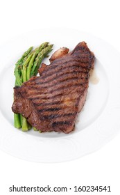holiday evening dinner meat table : grilled beef fillet with asparagus served on white plate isolated over white