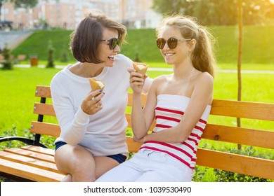 Holiday with the family. Happy young mother and cute daughter teenager in city park eating ice cream, talking and laughing