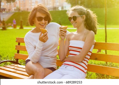 Holiday with the family. Happy young mother and cute daughter of a teenager in a city park eating ice cream, talking and laughing