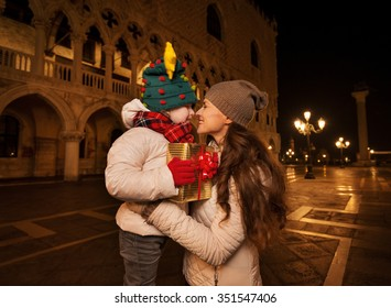 Holiday family trip to Venice, Italy can change the whole Christmas experience. Happy mother hugging child with Christmas gift box while standing on Piazza San Marco in the evening